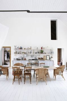 The high ceilings and white canvas off set the eclectic mix of chairs and kitchen accessories - a lovely blend.