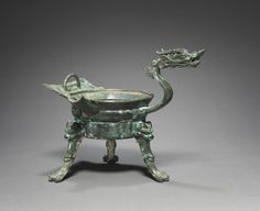 Tripod Container with Dragon-Head Handle (Zhadou), 500s China, Southern and Northern Dynasties period (386-589) bronze, Overall - h:22.80 cm (h:8 15/16 inches) Diameter of mouth with rim - w:15.50 cm (w:6 1/16 inches). Purchase from the J. H. Wade Fund 1983.214 Cleveland
