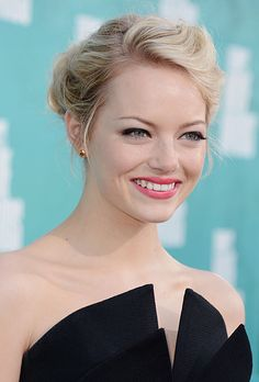 Brides.com: 25 Wedding Hairstyles Inspired by Celebrities. Emma Stone's Wavy Chignon. Emma Stone's wavy, side-swept chignon works for almost every neckline, which makes it both timeless and utterly modern. Stone, star of The Amazing Spider Man, accented her soft updo with bright coral lips, a look we love for spring and summer brides. Browse more romantic updos.