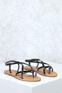 sports shoes 7542e c06b3 A pair of faux leather sandals with a thong toe, crisscross vamp, and an