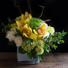 Verona | A dreamy floral arrangement that is modern and beautiful. Verona is designed with stunning golden cymbidium orchid blooms, surrounded by a mix of ...