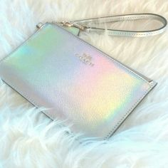 "2XHP!NWT Authentic Coach Hologram Wristlet *This brand new authentic Coach wristlet is so so cute!  It is a shiny silver with a hologram, and has a rainbow effect (depending on the angle).  It is made of PVC material.  It has gold hardware, and two card slots inside.  It is approx 4 1/2"" long x 7"" wide.  It would be great for your keys, credit card, lip gloss, etc.!* Coach Bags Clutches & Wristlets"