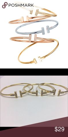 """T Bangle Inspired Gold T Bangle with Crystal detail. High quality metal base with 18k gold plate. Open face bangle fits best 7-7.5"""" ALL LAYOUTS WITH PHOTOS ARE COPY WRITTEN AND ARE NOT FOR USE BY THIRD PARTIES UNDER COPY WRITE LAW. Jewelry Bracelets"""