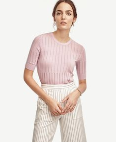 "Pointelle stitch detail adds an extra refined touch to this flattering knit - a perfect topper for feminine skirts and wide leg pants. Jewel neck. Short sleeves. Ribbed cuffs and hem. 21"" long."