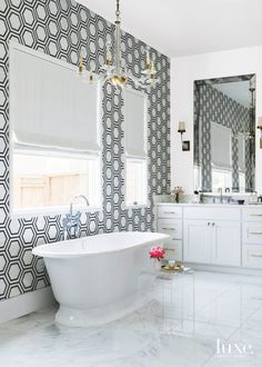 Hexagonal wallpaper in a black and white master bathroom steals the show.