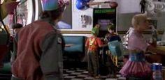 Cena de De Volta para o Futuro II (Foto: Reprodução)  Vídeo game sem joysticks  Em uma cena do filmeDe Volta para o Futuro II, Marty mostra para algumas crianças como jogar video game com uma arma de pistola e elas desdenham do fato de ele usar joystick. Apesar do personagem estranhar o fato, na vida real a chegada do Kinect causou animação entre os gamers. A tecnologia criada permite maior interação com o jogo, já que o jogador utiliza o corpo inteiro para fazer os movimentos.