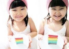 Adorable little girl with rainbow cake