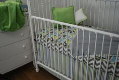 Grey Chevron and zoo print crib sheet in the crib with a stripe skirt and blanket trim