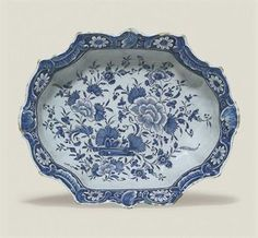 A DUTCH DELFT SHAPED RECTANGULAR BASIN  CIRCA 1750  The basin in blue on a robin's egg blue ground, with flowering branches of peony and other flowers issuing from scrolls, the border molded with foliate scrolls and shells along the shaped rim and reserved with daisies, the underside with a cloud pattern and Auspicious Objects  12½ in. (31.8 cm.) wide