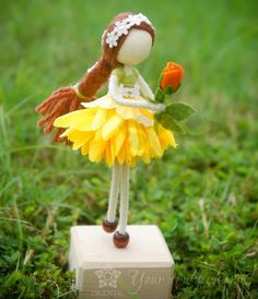 The girl has a long hair in a plait with a white crochet headband, shes holding an orange tulip <3. And she has no face. Do you know the story