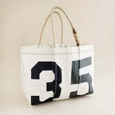 """Sea bags® tote ( item 48690) Crafted in Portland, Maine, from reclaimed sails, each bag is made entirely by hand (so no two will ever be exactly alike). The authentic signs of hard sailing, including rust, salt and stains, are what we like to call character. Each durable, water-resistant bag sports heavy-duty handles and a hook-and-ring closure. Recycled Dacron sail. Nylon/poly handles. Stainless steel closure. Interior zip pocket, exterior pocket. USA. 10"""" handle drop. 14""""H x 18""""W x 7""""D…"""