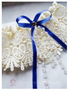 unusual beautiful wedding garter with blue bow, source: http://www.vertigo.com.pl/projekty/podwiazki/#prettyphoto[gallery]/1/