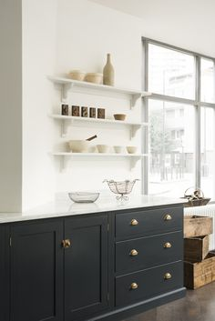 Shaker cabinets with drawers that look like furniture.  Brass hinges that are visible. Trim on the bottom.