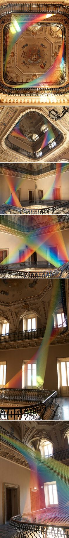 Take a moment to look at this - it's not created by light as it first appears, but by colored strings strung to look like a fabulously refracted rainbow from a giant glass prism.  By Gabriel Dawe