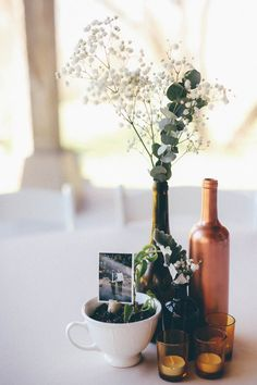 The Day We Wed | All the Delights Centerpiece idea: rose gold wine bottles, eucalyptus, baby's breath, succulents, photos, candles