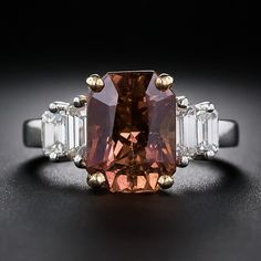 A rare and enchanting, natural no-heat sapphire, described by the A.G.L. (American Gemological Laboratory) as 'Pinkish Orange-Brown'; in layman's terms, however, we'd say, 'Hawaiian Sunset' or 'Cinnamon-Paprika'(!). In any case, a truly gorgeous and exotic color and no photo can really do it justice. This fabulous 6.00 carat gemstone is tastefully presented in a platinum and 18 karat yellow gold mounting glimmering with a pair of high-color emerald-cut diamonds on each shoulder.