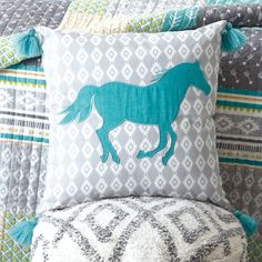 Diamond Print Horse Pillow- Dashing in the wind, this turquoise horse looks beautiful against a grey and white Aztec-diamond background. Tassels on the edges of the pillow give some extra flare.