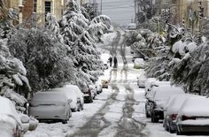 Jordanians walk past snow-covered cars and trees in Amman