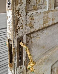A knotted length of rope serves as a casual replacement for hardware on the master bath door.   - CountryLiving.com