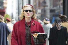 Cate Blanchett as Carol wearing cat eye sunglasses red dress coat, beret and clutch bag