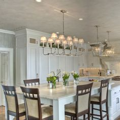 Borrow this idea: Incorporate different yet complementary styles of accent lighting to visually distinguish work area from dining area.