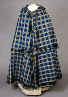 Mantello femminile in cotone con trama scozzese, foderato in lana rasata. La doppia ruota garantisce una buona capacità di scaldare e di riparare dalle intemperie. Costo £230