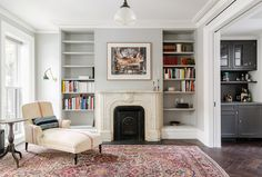 Traditional living room with fireplace, built-in bookshelves, and Persian rug