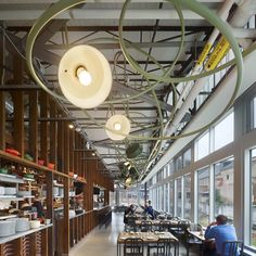 The stand-out feature at the café is its centre-piece light installation, a joint project between the designers and fabricators which weaves in and around the existing struts...