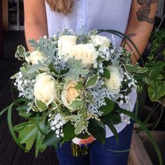 Classic with a twist? Baby's breath and off white Vendela roses here mixed with a selection of seasonal foliages!