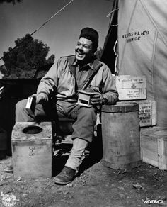 Herbert M. Sifford, Greensberg, PA, asst field director of the American Red Cross, grinding coffee at an ARC camp near Tebessa, Tunisia. 19 February 1943