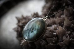 A home for your choice of For Strange Women natural solid perfume, featuring a large Labradorite on the lid of the locket. Labradorite is a gorgeous natural stone with an iridescent range of of deep blues and greens, sometimes interspersed with red and gold. It is believed to assist