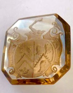 "A nice Victorian smokey quartz intaglio seal #intaglio  heraldic family crest Horse leg hoof at the top of the fancy shield Lion and dog head detail hunting horn  faceted cut to central culet for mounting into a ring  measuring approx 2 cm x 2 cm Conversion 25 mm = 2.5 cm = 1"" Weight 4.8 grams"