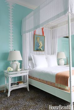 Palm Beach Walls in Benjamin Moore's Clearlake are overlaid with a white-palm motif in a Florida bedroom. A portrait of the designer's mother holding her dog hangs over the canopy bed.