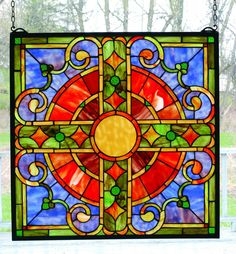 Description: THIS REVISED VERSION OF AN MEDIEVAL CROSS WINDOW OF CORAL AND JADE WITH GOLDEN HIGHLIGHTS AND GLISTENING EMERALS ACCENTS LIES AGAINST A TWILIGHT BLUE SKY BORDERED IN JADE. THE FRAME IS CO