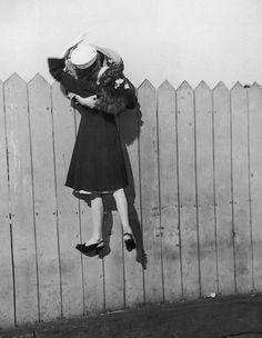 Un soldato si sporge da una staccionata e solleva la sua fidanzata per baciarla, 1945. Hulton Archive.