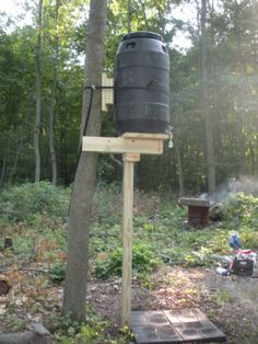 Off grid shower in the woods. Use a barrel to store the water in the shower house.