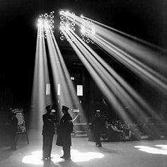 Deze zwart-wit foto is vooral donker. Er is veel zwart en grijs te zien in de foto. Het licht echter is wit. Dit zorgt ervoor dat het extra veel opvalt. De ramen laten het licht doorkomen en het licht maakt het leven, de mensen, zichtbaar.