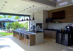 Com dimensões generosas, o gourmet conta com churrasqueira, fogão e forno a lenha, dois frigobares e o mesmo padrão de armários da cozinha.