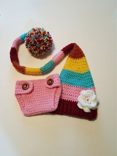 This adorable long tail hat and diaper cover set is crocheted using 100% soft, acrylic yarn.  The long tail hat is yellow, turquoise, pink, cranberry red and orange. A white flower is attached to the hat.  The diaper cover is a solid pink color.  Wooden buttons allow you to open and close the diaper cover with ease.