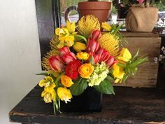 Arrangement by Botany including parrot tulips, hydrangea, ranunculus, and pincushions.