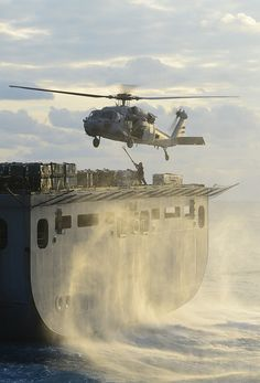 An MH-60S retrieves cargo from USNS William McLean. by Official U.S. Navy Imagery
