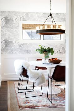 Modern dining space with sheepskin rug on black chairs and industrial chandelier with exposed light bulbs.