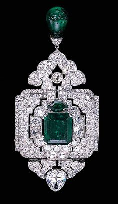 AN IMPRESSIVE EMERALD AND DIAMOND PENDANT/BROOCH, BY CARTIER   Designed as an old European and old mine-cut diamond openwork panel with a central rectangular-cut emerald weighing 12.28 carats, suspending a diamond palmette and emerald bead drop, to the pear-shaped diamond surmount, circa 1927.