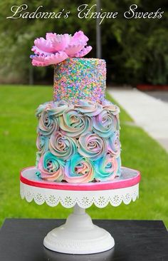 Colorful pastel rainbow cake. Adorned with a beautiful Peony flower, confetti and rosettes