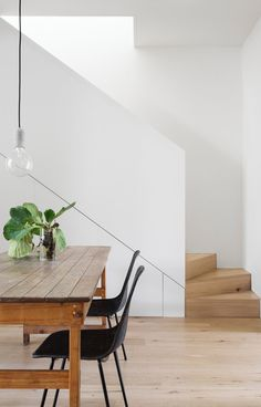Minimal white dining room with lots of wood and built in storage under the stairs.