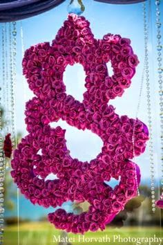 Use a modern ganesh in the form of flowers hanging from your mandap at your fusion wedding. Lord Ganesh brings good luck to newlyweds and wishes them farewell.