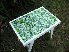 """""""This fabulously simple yet effective idea from Marianne Kirby proves that putting buttons on almost anything will dramatically improve its looks. At least, this certainly turned out to be true in the case of an old table she picked up for $5 at a yard sale."""" After scoring the table, Marianne bought 1,600 green and white buttons on eBay. She spray painted the table, then attached the buttons with a basic tacky craft glue. Then she created a table top with a pourable resin, and then ..."""