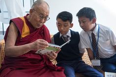 His Holiness the Dalai Lama looking at a book together with with two young boys during his visit to Shiwatso Library in Mundgod, Karnataka, India on December 22, 2016. Photo/Tenzin Choejor/OHHDL