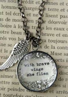 with brave wings she flies. I have this necklace. Love it :) Would love to get a tattoo with this saying incorporated into it.