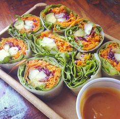 Healthy snack, rolled in rice paper: avocado, carrots, cucumber, cabbage & peanut sauce